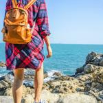 woman on vacation standing near rocky beach